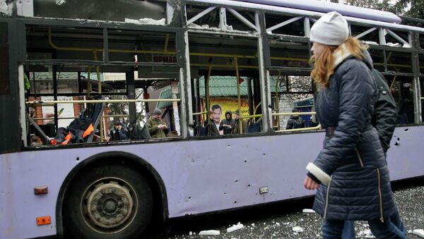 Девушка проходит мимо обстрелянного троллейбуса в Донецке