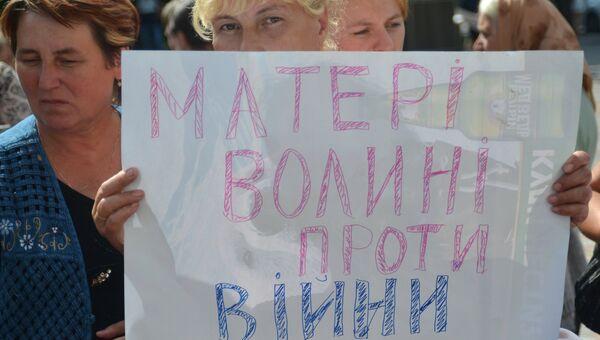 Женщина с плакатом Матери Волыни против войны во время акции у Верховной Рады Украины