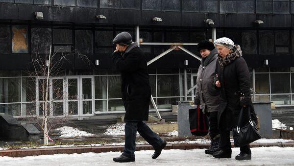 Жители Донецка на фоне поврежденного в результате обстрела здания