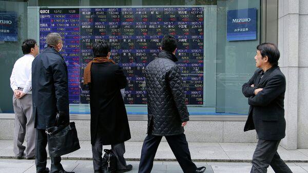 Прохожие в Токио смотрят на экран с биржевыми котировками. Архивное фото