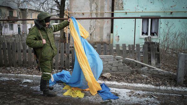 Ополченец держит флаг Украины, брошенный украинскими военными в Углегорске