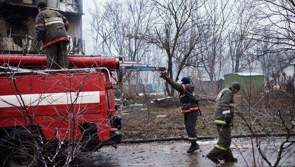 Пожарные у дома, расположенного недалеко от обстрелянного химического завода в Донецке