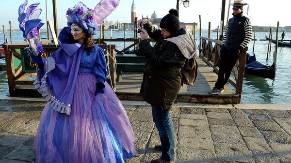 Турист фотографирует участницу карнавала недалеко от площади Святого Петра в Венеции