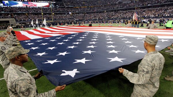 Военные США держат американский флаг перед началом игры чемпионата по американскому футболу. Техас, США