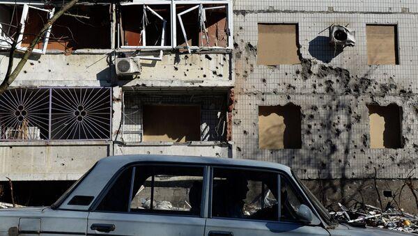 Машина перед поврежденным зданием в Донецке. Архивное фото