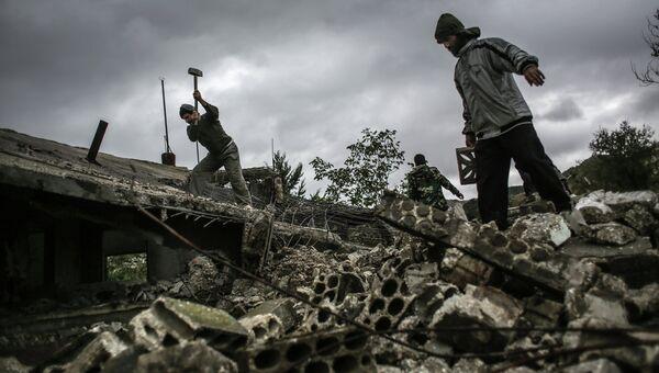 Местные жители разбирают завалы дома, который был взорван в результате штурма села Удин в провинции Латакия. Архивное фото