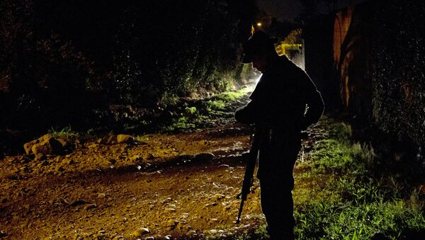 Колумбийский полицейский дежурит на месте обнаружения трупов