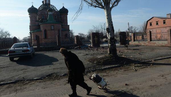 Женщина везет тележку с углем в поселке Октябрьский рядом с аэропортом города Донецка. Архивное фото.