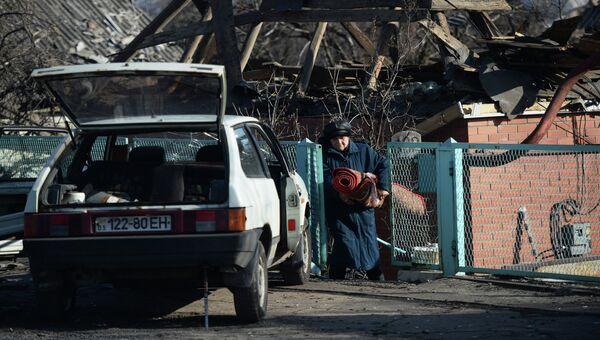 Женщина выносит вещи из своего разрушенного дома в поселке Октябрьский рядом с аэропортом города Донецка. Архивное фото