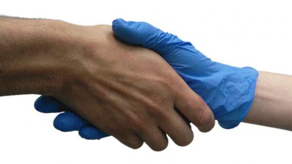 Ученый пожимает руку добровольцу в стерильной перчатке