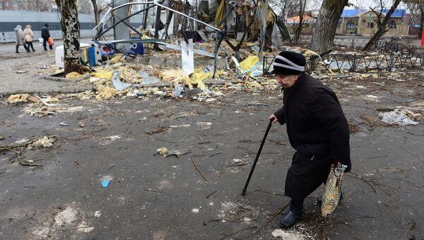 Пожилая женщина идет к автобусной остановке в Киевском районе Донецка