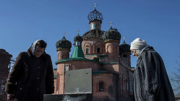 Женщины у поврежденной церкви Октябрьского района Донецка. Украина. Архивное фото