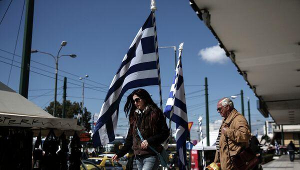 Люди на одной из улиц города Афины в районе Пирея. Архивное фото
