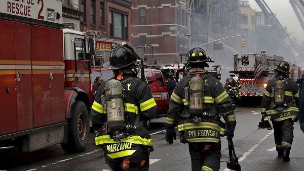 Пожарные работают на месте взрыва газа в жилом доме в Нью-Йорке, США