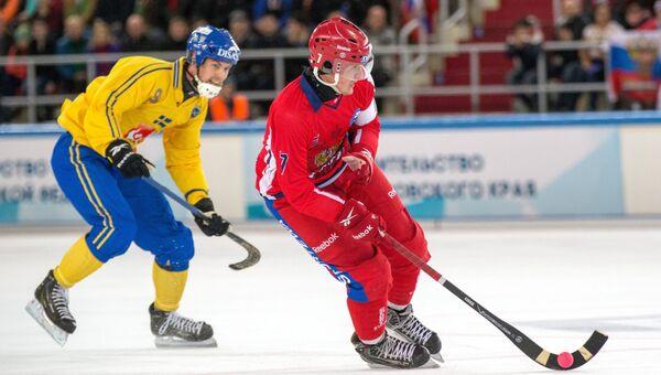 Игрок сборной Швеции Юнас Нильссон (слева) и игрок сборной России Сергей Ломанов в матче чемпионата мира по хоккею с мячом