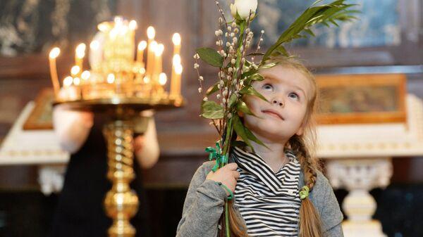 Девочка перед патриаршим служением в канун празднования Входа Господня в Иерусалим в Храме Христа Спасителя в Москве