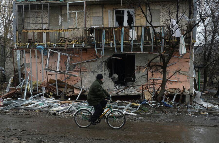 Житель города Дебальцево едет на велосипеде мимо разрушенного в результате обстрелов во время боевых действий жилого дома