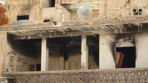 Пострадавшее от боевых действие здание в сирийском городе Маалюля в 55 км от Дамаска