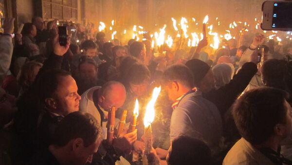 Паломники с Благодатным огнем в храме Воскресения Христова (Гроба Господня) в Иерусалиме. Архивное фото