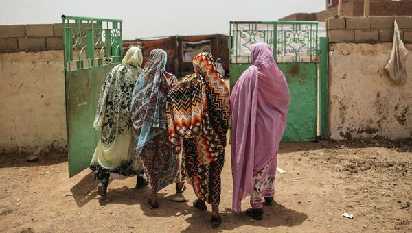 Женщины покидают избирательный участок в первый день президентских и парламентских выборов в Судане