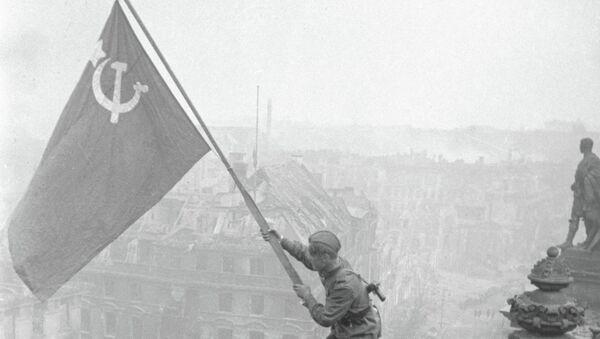 Боец Красной армии водружает Знамя Победы на поверженном рейхстаге