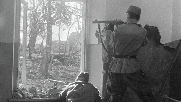 Бойцы ведут огонь по противнику из проема окна на окраине Новороссийска