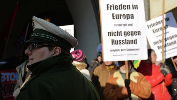 Полицейский на  многотысячной демонстрации на площади у городской ратуши в Мюнхене с лозунгами прекратить конфронтацию с Россией