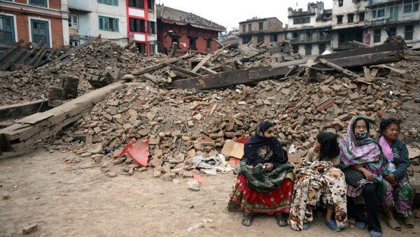 Жители сидят возле разрушенного здания в Катманду, Непал