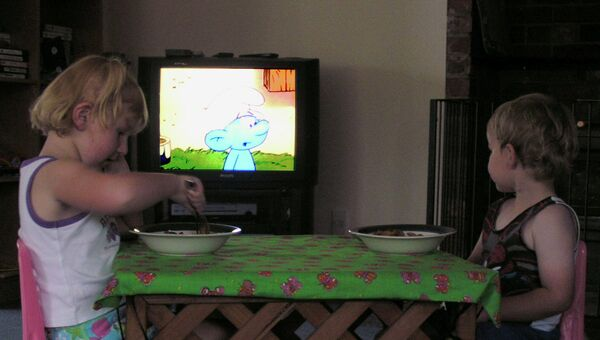 Дети кушают и смотрят телевизор