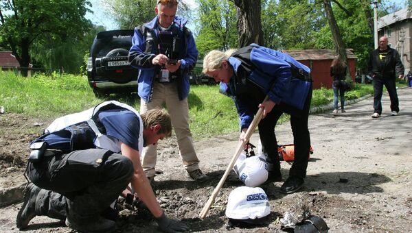 Сотрудники миссии ОБСЕ у дома, разрушенного в результате обстрела украинскими силовиками в Донецке