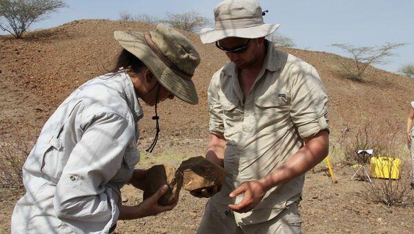 Арман и Льюис изучают извлеченное орудие труда