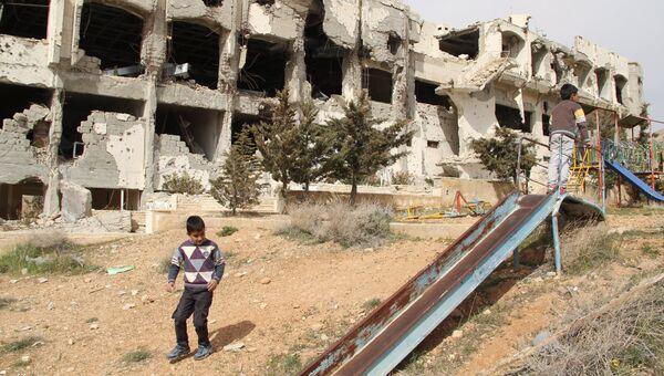 Мальчики играют на детской площадке на фоне гостиницы Сафир, полностью разрушенной при боевых действиях в сирийском городе Маалюля. Архивное фото