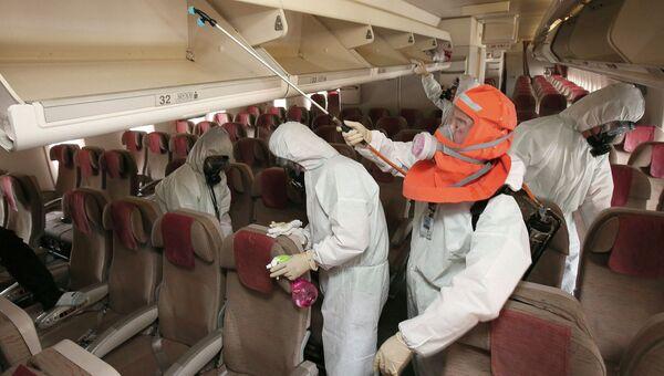 Сотрудники санитарной службы обрабатывают салон самолета в международном аэропорту Инчхон