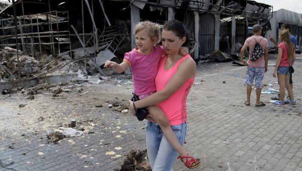 Женщина с ребенком проходит мимо рынка, разрушенного в результате обстрелов, в Донецке