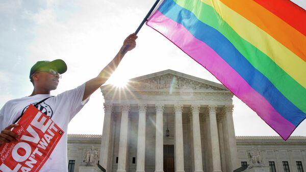 Активист держит флаг ЛГБТ у здания Верховного суда США в Вашингтоне