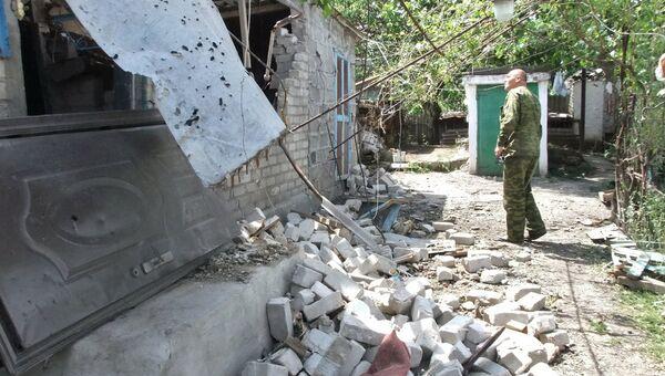Мужчина у дома, поврежденного в результате обстрела украинскими силовиками, в селе Саханка Донецкой области
