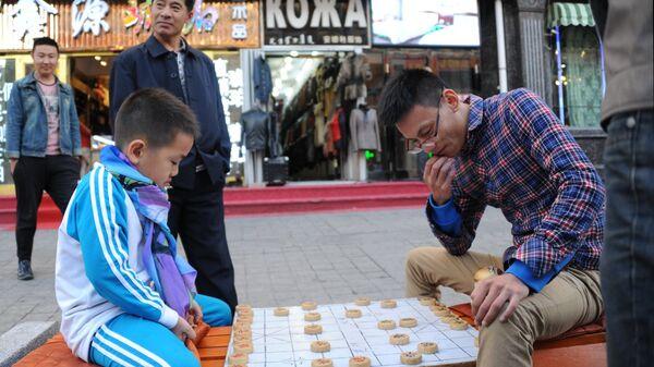 Мальчик и мужчина играют в Сянцы (китайские шахматы) на одной из улиц Маньчжурии