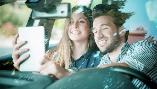 Молодая пара делает селфи за рулем автомобиля