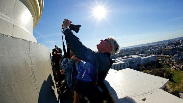 Мужчина делает селфи с помощью фотоаппарата на куполе Капитолия в США. 2013 год