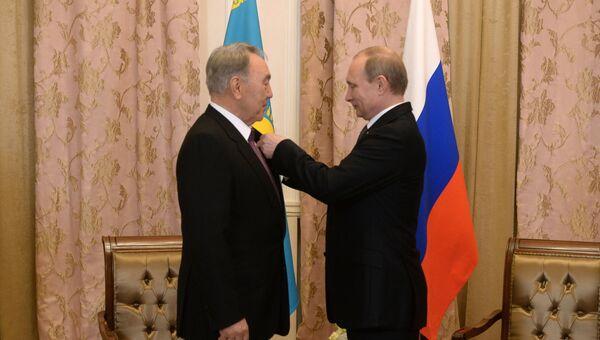 Президент Российской Федерации Владимир Путин (справа) вручает Президенту Республики Казахстан Нурсултану Назарбаеву орден Александра Невского во время встречи в Уфе