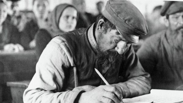 Пожилой мужчина выводит первые буквы на занятиях кружка ликбеза