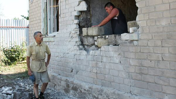 Мужчина ремонтирует стену жилого дома в Горловке после обстрела. Архивное фото