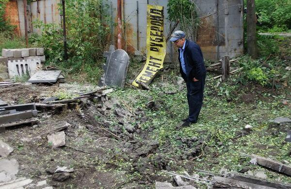 Мужчина рассматривает воронку от разорвавшегося снаряда в результате обстрела Донецка