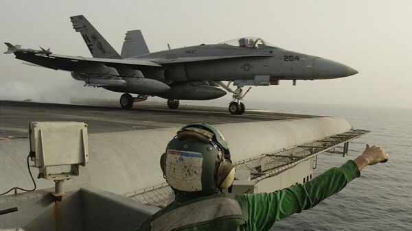 Американский штурмовик F/A-18 Hornet взлетает с палубы авианосца Китти Хоук в Персидском заливе. 21 марта 2003