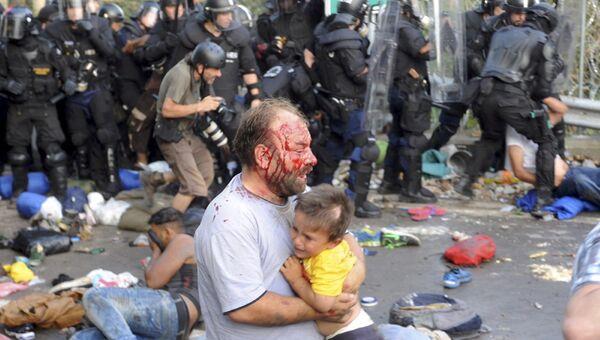 Мужчина с ребенком, пострадавший во время столкновения с полицией на границе Венгрии и Сербии. 16 сентября 2015