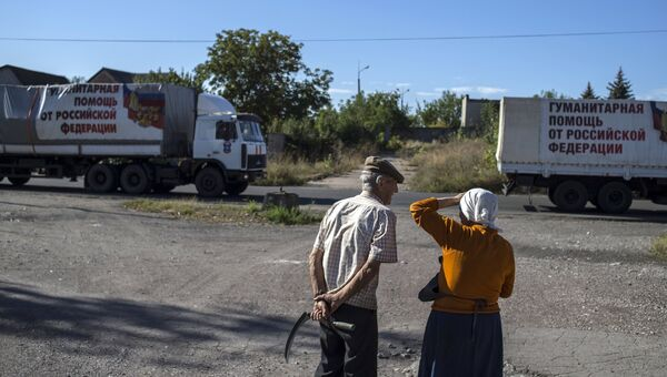 Местные жители наблюдают за проходом колонны машин 38-го гуманитарного конвоя в Донецкой области