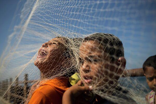 Палестинские дети играют с рыболовной сетью на пляже в Газе