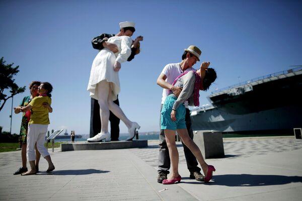 Пара на фоне скульптуры Безоговорочная капитуляция, созданной по мотивам культовой фотографии Поцелуй на Таймс-сквер, в Сан-Диего, США