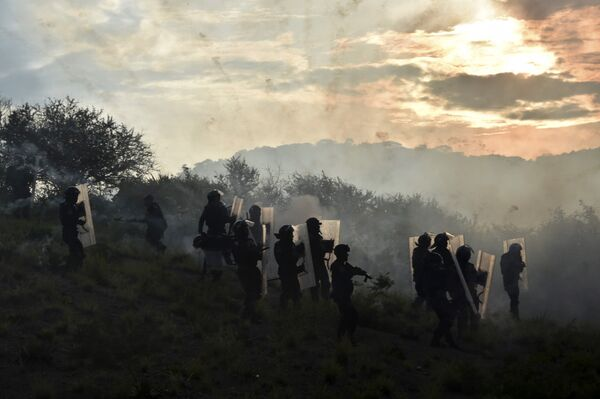 Полицейские во время столкновения со студентами на объездной дороге в районе города Тистла, Мексика