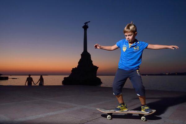 Мальчик катается на скейтборде на набережной в Севастополе